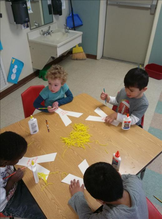 Children are learning about the letter Y in the Preschool Classroom by putting yarn on Y.